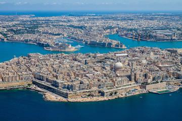 Malta aerial view. Valetta, capital city of Malta, Grand Harbour, Senglea and Il-Birgu (Vittoriosa) towns, Fort Ricasoli and Fort Saint Elmo from above. Marsaxlokk city and Freeport in background