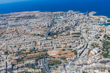 Aerial view of urban Malta. Tunnel on highway 1 under Ta' Giorni town and Paceville district, parts of St. Julian's (San Giljan) city from above. Blocks of apartment buildings, sleeping quarters