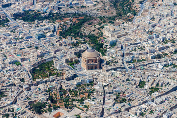 Famous Mosta Dome (Rotunda of Mosta, The Basilica of the Assumption of Our Lady Mary) aerial view. Roman Catholic parish church and Minor Basilica in Mosta, Malta. Malta from above