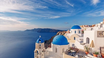 Fototapete - Churches in Oia, Santorini island in Greece, on a sunny day with dramatic sky. Scenic travel background. 4K timelapse.