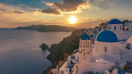 Fototapete - Beautiful view of Churches in Oia village, Santorini island in Greece at sunset, with dramatic sky. 4K day to night transition timelapse.