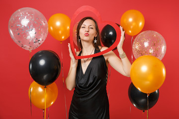 Pretty young girl in black dress holding big red wooden heart, blowing lips, sending air kiss on red background air balloons. St. Valentine's Day, Happy New Year birthday mockup holiday party concept.