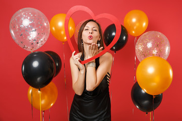 Tender young girl in black dress holding big red wooden heart, blowing lips, sending air kiss on red background air balloons. St. Valentine's Day, Happy New Year birthday mockup holiday party concept.
