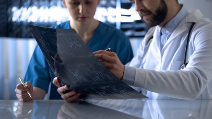Neurosurgeon and nurse watching cerebral vessels x-ray before operation