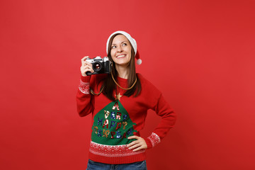 Pretty merry young Santa girl in Christmas hat looking up and holding retro vintage photo camera isolated on red background. Happy New Year 2019 celebration holiday party concept. Mock up copy space.