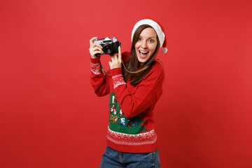Cheerful young Santa girl in knitted sweater and Christmas hat holding retro vintage photo camera isolated on red background. Happy New Year 2019 celebration holiday party concept. Mock up copy space.