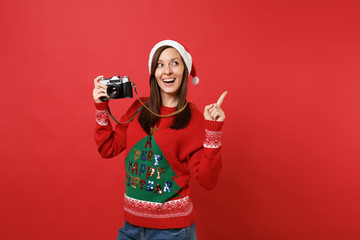Pretty young Santa girl in Christmas hat pointing index finger up hold retro vintage photo camera isolated on red background. Happy New Year 2019 celebration holiday party concept. Mock up copy space.