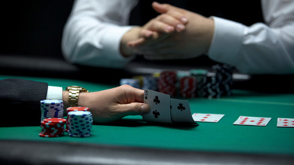 Poker player checking bad combination of cards dealt by croupier, weak hand