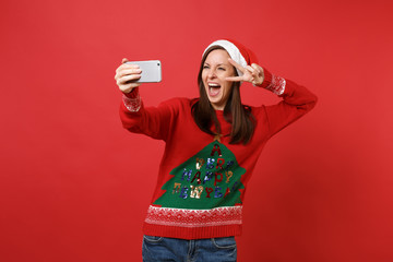 Funny Santa girl with opened mouth doing taking selfie shot on mobile phone, showing victory sign isolated on red background. Happy New Year 2019 celebration holiday party concept. Mock up copy space.