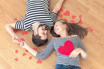 Happy valentines couple lying on the floor and looking at each other.