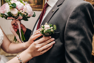 The bride hangs a boutonniere on the jacket of the groom, who holds the bouquet for the bride in his hands