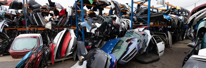 Auto parts market. On the ground are doors, bumpers and windshields.