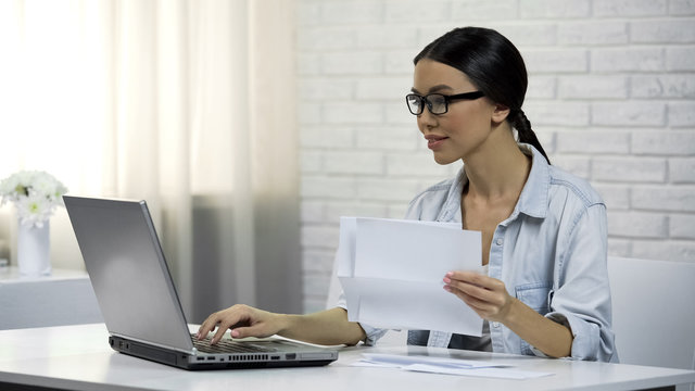 Woman typing on laptop at home, paying for utilities online, easy banking