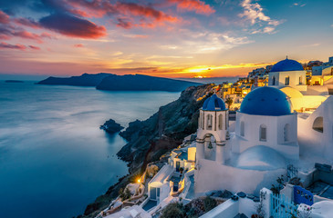 Fototapete - Beautiful view of Churches in Oia village, Santorini island in Greece at sunset, with dramatic sky.