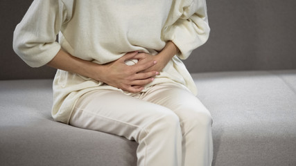 Lady suffering from strong stomach ache, gastritis, problems with gall bladder