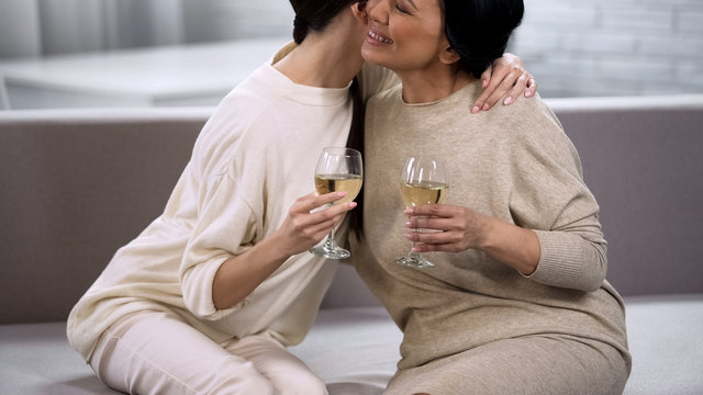 Beautiful female friends hugging resting on sofa and drinking sparkling beverage