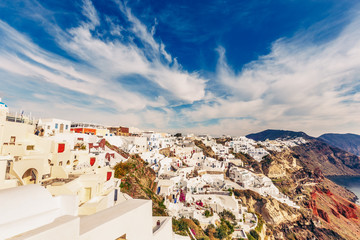 Architecture of Oia village, Santorini island in Greece, on a sunny day with dramatic sky. Scenic travel background.