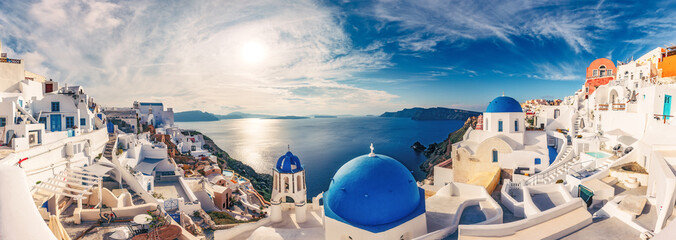 Fototapete - Churches in Oia, Santorini island in Greece, on a sunny day with dramatic sky. Panorama view.