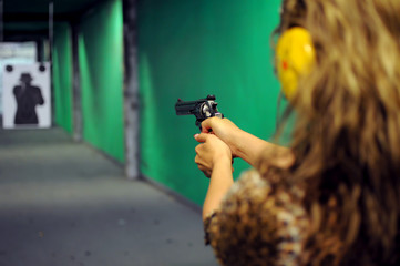 The girl shoots at the shooting range with a 45 caliber revolver