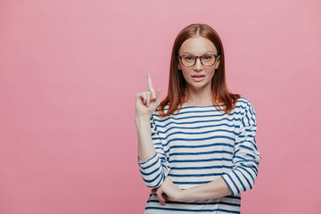 Attentive beautiful woman wears spectacles and striped sweater, points with fore finger upwards, stands against pink studio wall with free space for your advertisement or promotional content