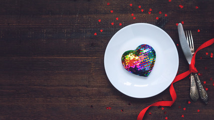Valentine's Day Festive table setting with rainbow heart on white plate, fork, knife and red ribbons on rustic wooden table. Meal on Valentines Day for Lgbt homosexual couple. Flat lay, copy space