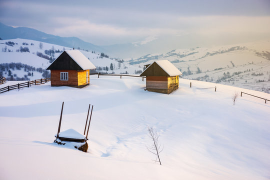 outskirts of the village on the hill. summerhouse, woodshed and haystack behind the wooden fence on a snowy slope. peaks of the distant mountain ridge in clouds. wonderful winter tale