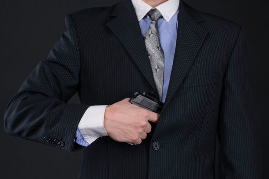 man in suit pull the gun out of his jacket