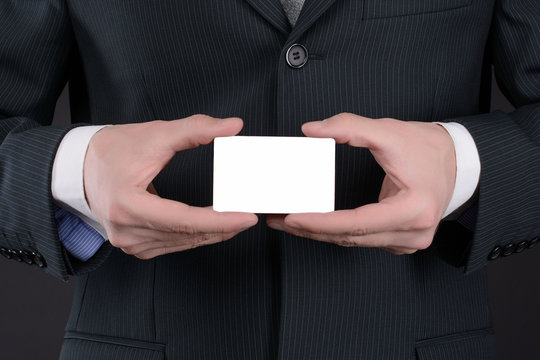 Man in suit holding business card by one hand and point pointing her with his index finger