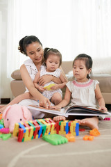 Pretty young mother and her little daughters looking at colorful picture in the book