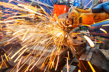 Close-up of a man sawing metal with a hand circular saw on a wooden table, bright flashes flying in different directions, in the background tools for an auto repair shop. Work of auto mechanics.