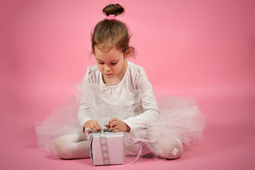 Cute little girl in white tulle skirt opens a gift on a pink background