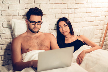 Young Couple in Bed, Man Working Laptop Bored Wife