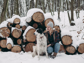 Woman and her dog in winter forest.