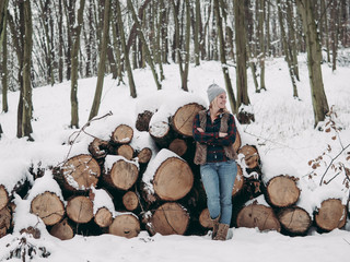 Young woman standing by cut tree trunks in forest.