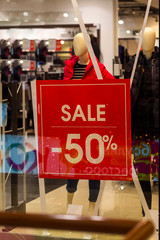 "the inscription ""sale"" in the window of a clothing store"