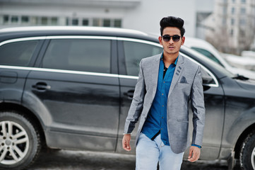 Casual young indian man in sunglasses posed against suv car.