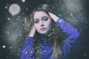 Beautiful, young girl with blond hair in a blue sweater on a snowfall in winter