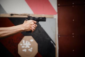 Man directs firearm gun pistol at target firing range or shooting range