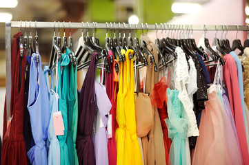 Few beautiful bridesmaid or evening dresses or ball gown on a hanger in a bridal shop
