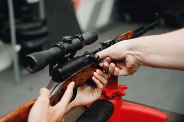 Automatic weapons aim firing gun pistol trainer helps man with loading cartridges. Shooting range