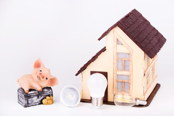 Led lamps and piggy bank lie near the house layout on a white background.