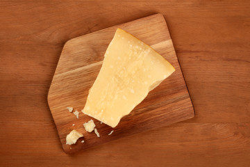 A piece of aged Parmesan cheese with crumbs, shot from the top on a dark rustic wooden background with a place for text