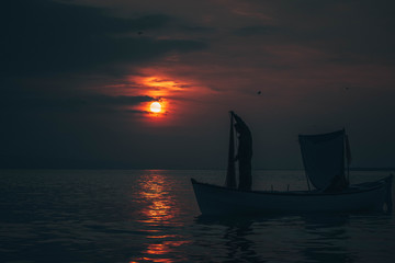 Sun goes down while fisherman throws his fishnet to collect fishes