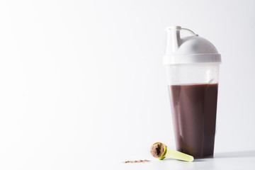 Chocolate protein shake and dumbbells isolated on white background
