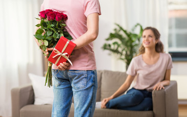 couple, relationships and people concept - happy woman looking at man hiding flowers and gift behind his back at home