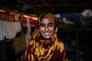 Formin Akter, a Rohingya refugee girl, smiles as she poses for a picture before heading to Chittagong to attend school at the Asian University for Women, in Cox's Bazar