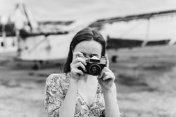 Young red headed beautiful caucasian girl with freckles. Blogger and photographer with photo camera shooting travelling scenes