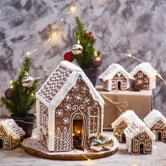 Wall Murals Christmas Big and small ginger houses - a village of ginger houses on a gray background with lights, Christmas decorations and small Christmas trees. Stilllife