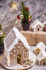 Big and small ginger houses - a village of ginger houses on a gray background with lights, Christmas decorations and small Christmas trees. Stilllife