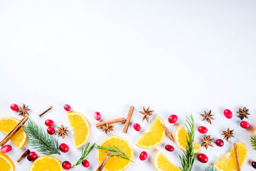 Winter autumn drink and food ingredients. Cranberries, sliced oranges, cinnamon, rosemary, anise for cooking cocktails, with christmas tree branches. Flatlay on white background. Top view copy space